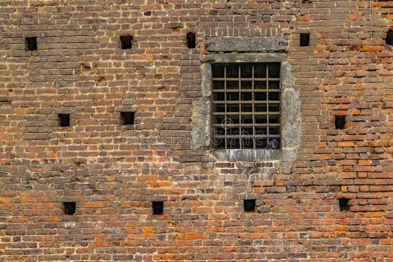 Взгляд кирпичной стены внешний с окном решетки утюга стоковое фото rf