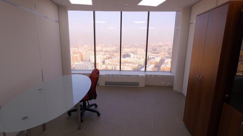 Взгляд комнаты из панорамного окна на ландшафте города Небольшая уютная комната с таблицей, стулом и шкафом с панорамным стоковые изображения