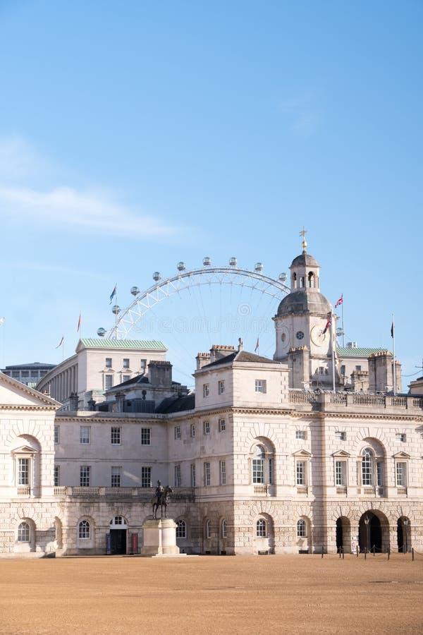 Взгляд конногвардейского полка сфотографированного на солнечный день зимы Колесо ferris глаза Лондона можно увидеть в расстоянии стоковое изображение