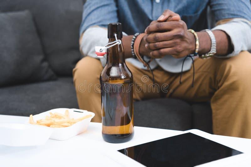 Взгляд конца-вверх Афро-американского парня есть французов жарит с пивом на таблице стоковые фото