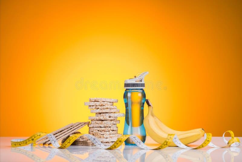 взгляд конца-вверх бутылки спорт с водой, печеньями диеты, измеряя лентой и бананом стоковые изображения