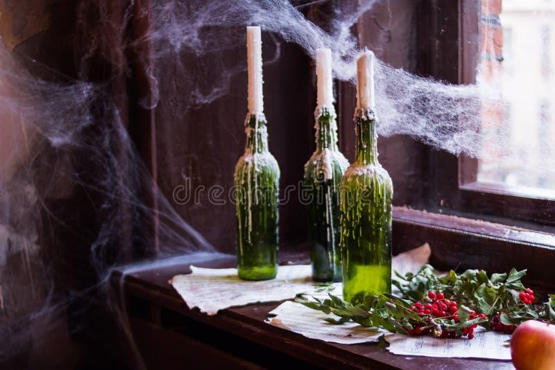 Взгляд конца-вверх горящих свечей в бутылках и украшений хеллоуина на таблице свечи, бутылки, гранаты, паутины стоковая фотография rf
