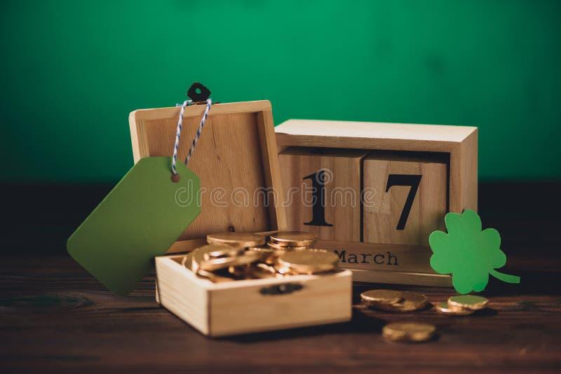 взгляд конца-вверх календаря, зеленого символа shamrock, пустого ярлыка и золотых монеток иллюстрация вектора