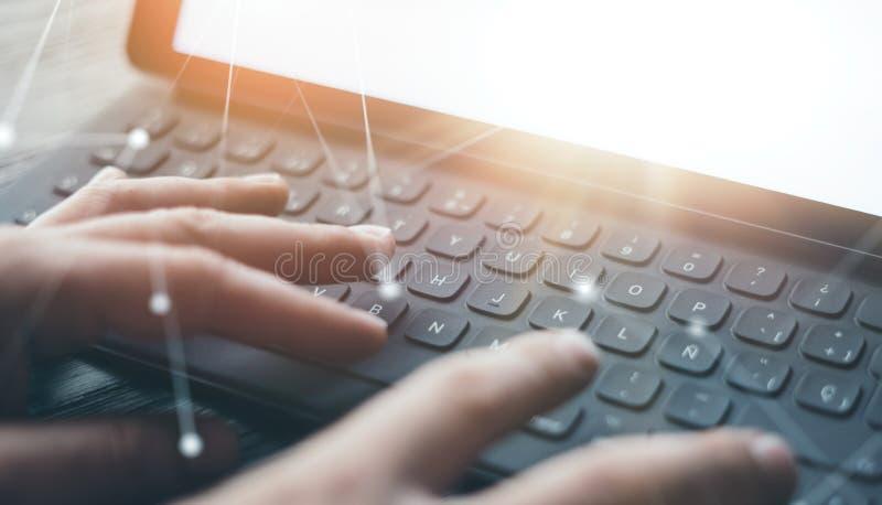 Взгляд конца-вверх мужских рук печатая на электронной станции клавиатур-дока планшета Бизнесмен работая на офисе и использовании стоковое фото