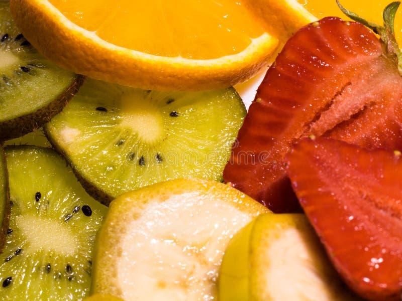 Взгляд конца-вверх на тропических плодах: банан, киви, апельсин, и клубники стоковое изображение rf