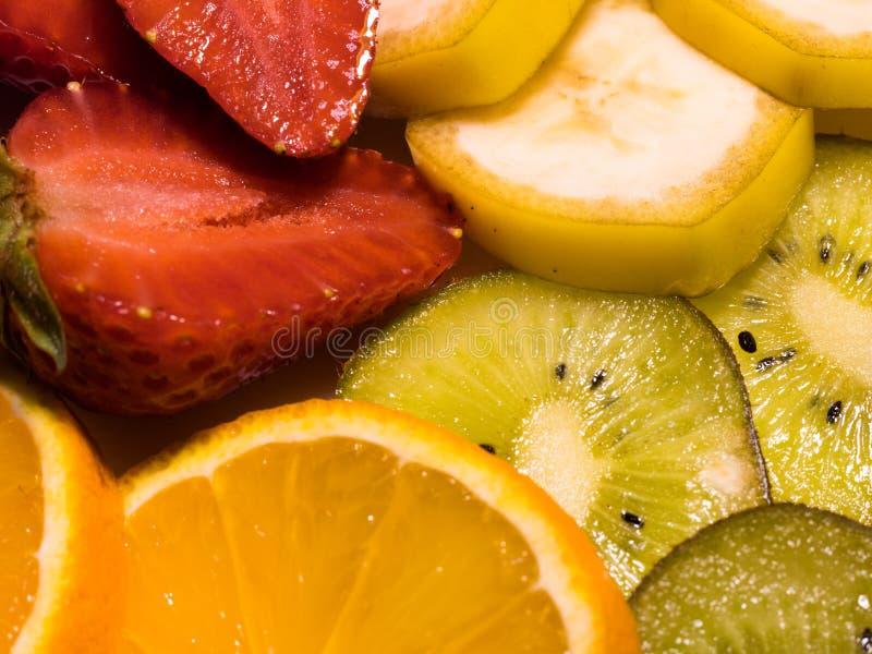 Взгляд конца-вверх на тропических плодах: банан, киви, апельсин, и клубники стоковые изображения rf