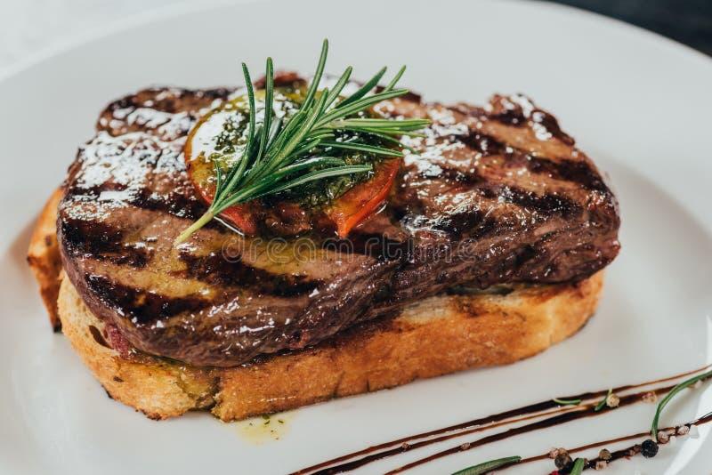 взгляд конца-вверх очень вкусного сочного стейка говядины с розмариновым маслом и зажаренным в духовке хлебом стоковая фотография rf