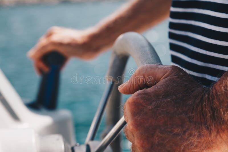 Взгляд конца-вверх старшего человека вручает управлять маленькой шлюпкой - капитаном стоковые изображения rf