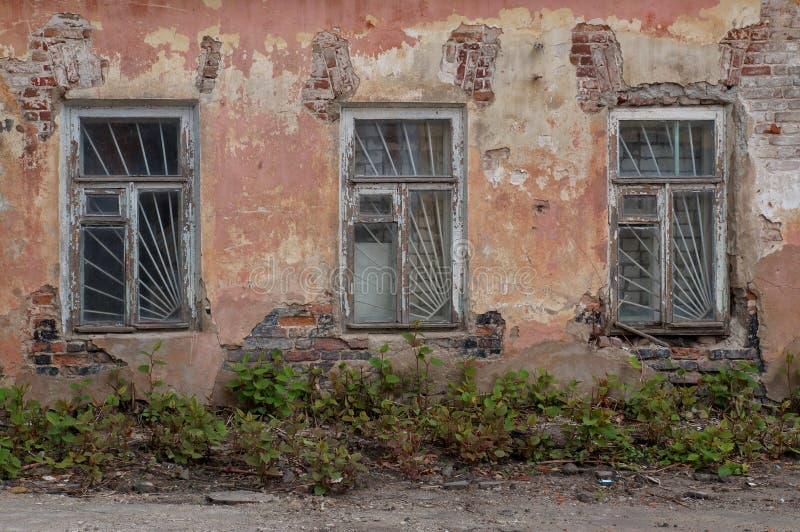 Взгляд конца-вверх фасада старого получившегося отказ дома 3 окна с решеткой, затрапезные заштукатуренные кирпичные стены стоковое изображение rf