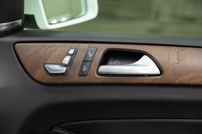 Взгляд конца-вверх части интерьера современного роскошного автомобиля с целью цвета серебр ручки двери на финише хрома стоковые фотографии rf