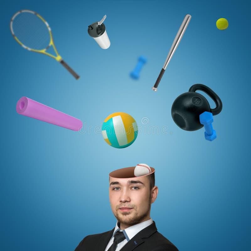Взгляд красивой головы молодого человека треснул открытое с различным спортивным инвентарем хлопающ вне изолированным на голубой  стоковое фото rf