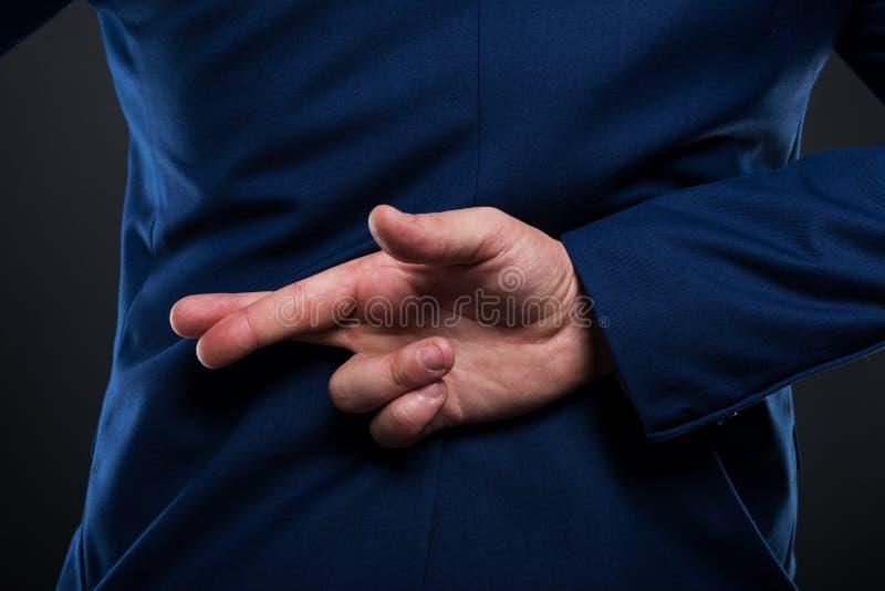 Взгляд крупного плана бизнесмена стоя с пересеченными пальцами стоковые фотографии rf