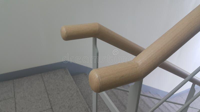 Взгляд крупного плана деревянного поручня серых конкретных лестниц стоковое фото