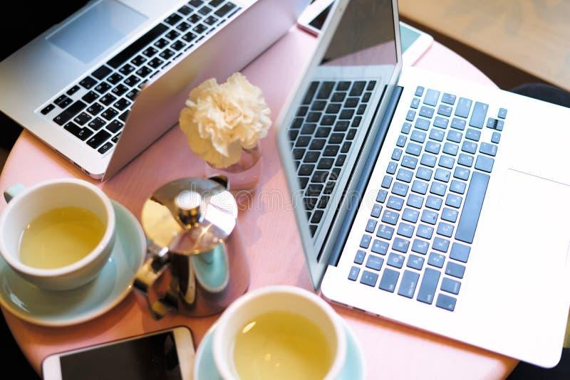 Взгляд крупного плана 2 раскрытого экрана ноутбука, космоса для плана дизайна Встреча в со-работать или кафе, дневной свет, чай ч стоковое изображение rf