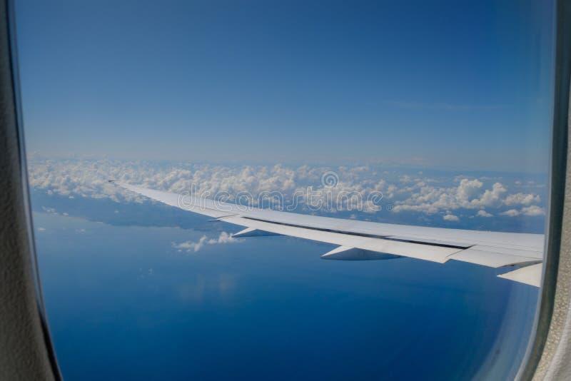 Взгляд крыла воздушных судн и облаков от иллюминатора стоковая фотография