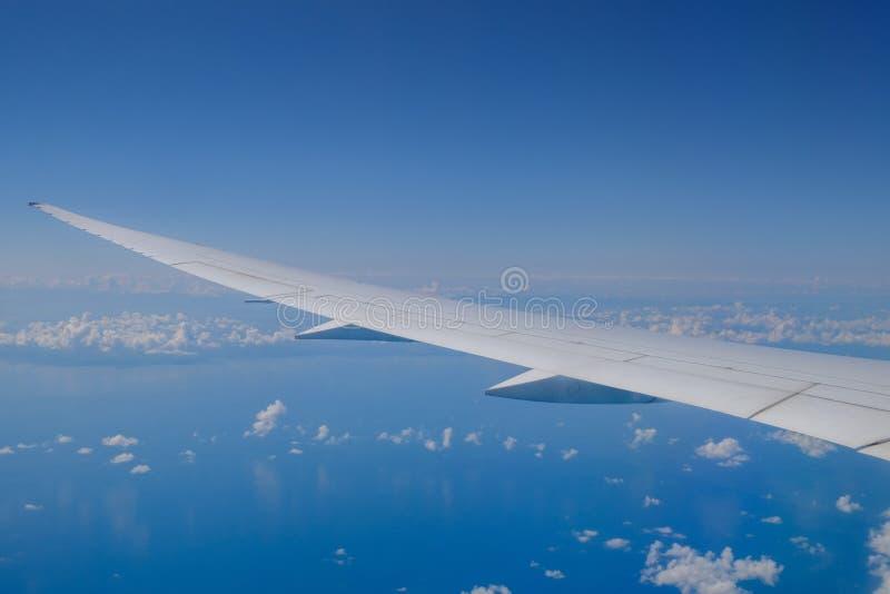Взгляд крыла воздушных судн и облаков от иллюминатора стоковые фото