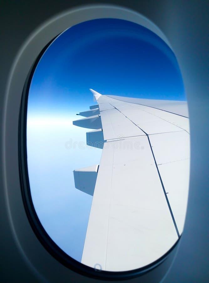 Взгляд крыла пассажирского самолета от иллюминатора в небе стоковые изображения