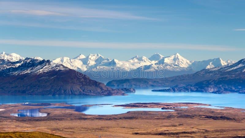 взгляд к красивой долине с озерами бирюзы со снег-покрытыми горами в Патагонии стоковое фото rf