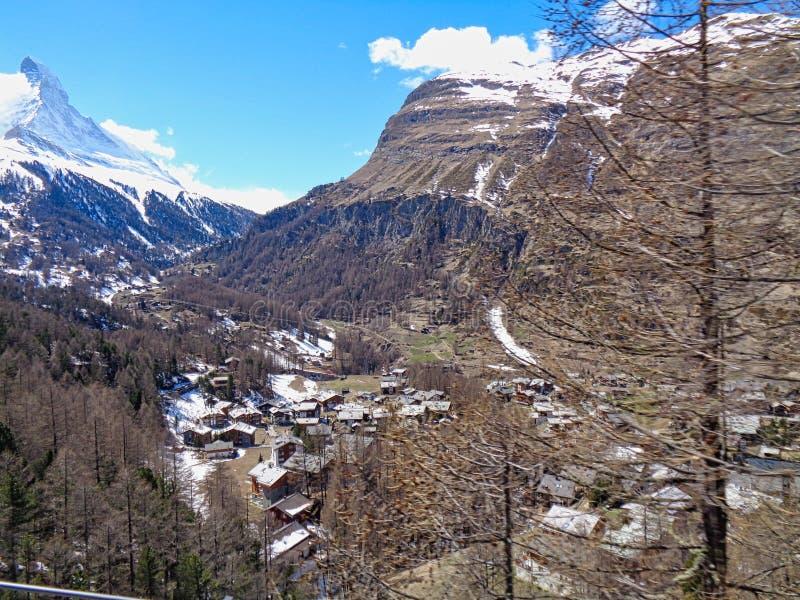 взгляд к небольшой деревне в швейцарских горных вершинах стоковые фото