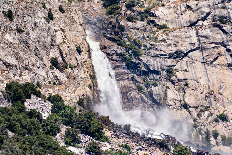 Взгляд к падениям Wapama падая вдоль стен гранита; Зона резервуара Hetch Hetchy, национальный парк Yosemite, сьерра-невада стоковое изображение rf