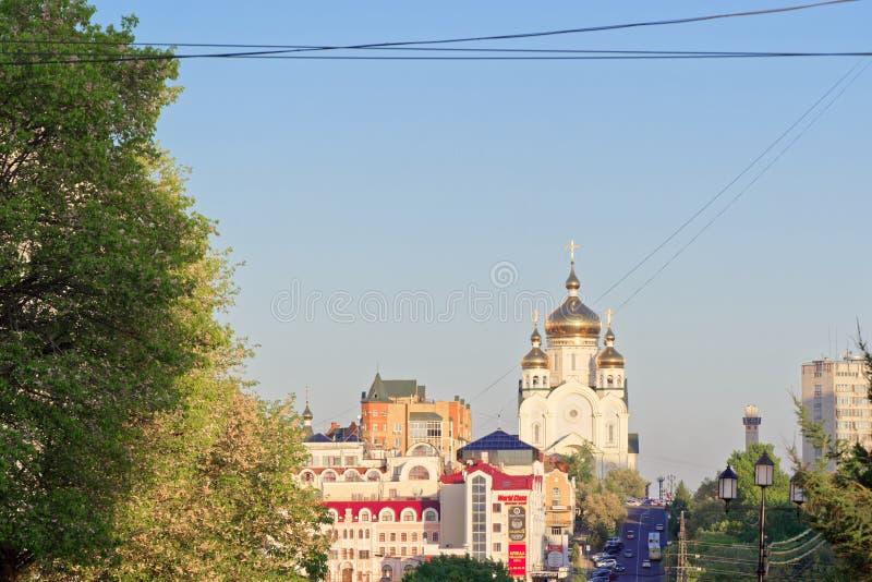 Взгляд к Русской православной церкви с золотым куполком крыш и жилыми buildins в расстоянии, Хабаровском, Россией стоковое изображение rf
