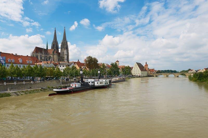 Взгляд к собору Регенсбурга и историческим зданиям с Дунаем на переднем плане в Регенсбурге, Германии стоковая фотография rf