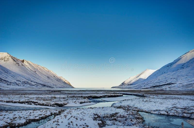 Взгляд ландшафта зимы Исландии с голубым небом и солнечным светом холодным fr стоковое фото rf