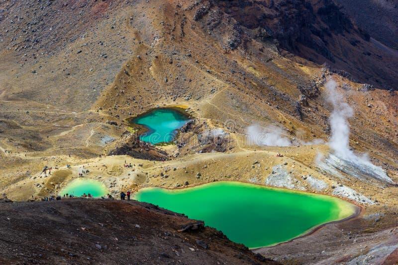 Взгляд ландшафта красочных изумрудных озер и вулканического ландшафта с hikers идя мимо, национальный парк Tongariro, Новая Зелан стоковое изображение rf