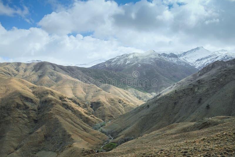 Взгляд ландшафта снега покрыл горную цепь против пасмурного голубого неба стоковая фотография rf