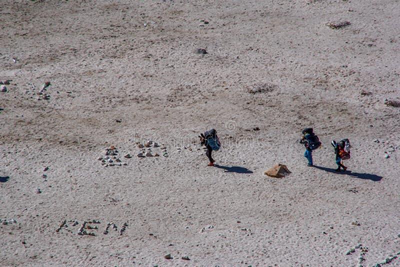 Взгляд ландшафта 3 sherpas нося тяжелые сумки стоковое фото