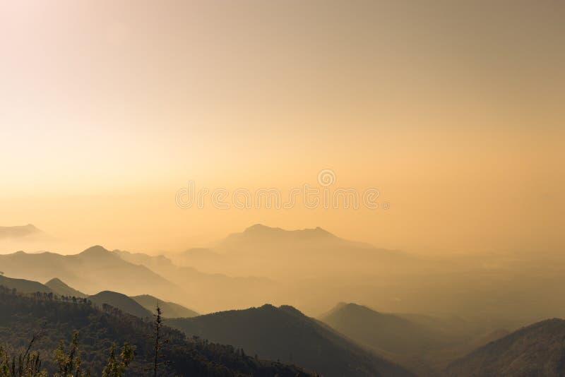 Взгляд лучей солнца туманных гор оранжевый стоковые изображения