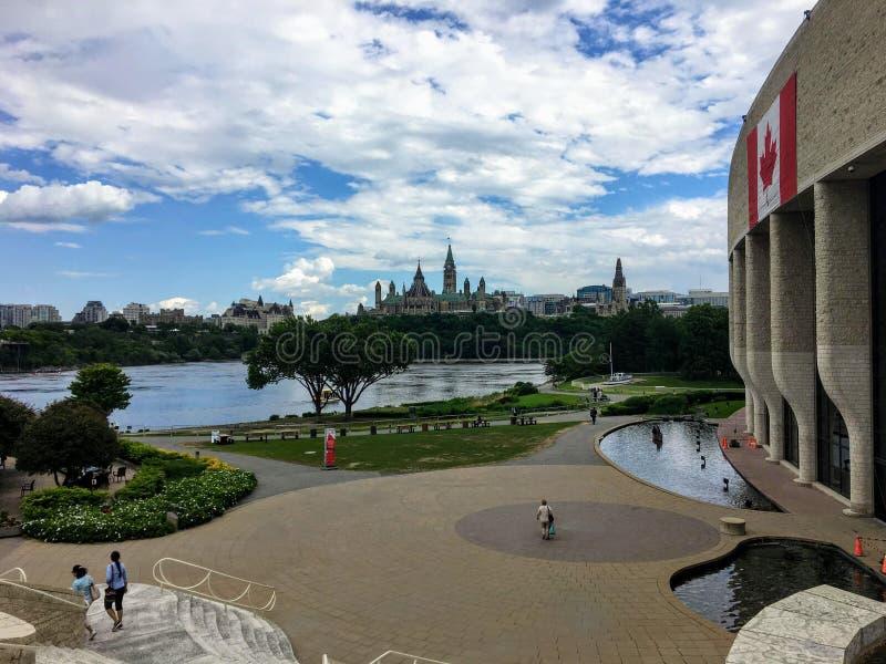 взгляд людей идя вне музея цивилизации в Gatineau, Квебека с холмом парламента в Оттаве, стоковое изображение rf