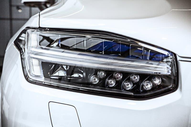 Взгляд макроса современной фары SUV автомобиля с влиянием graine шума фара лампы ксенона автомобиля взгляд детали на лампе ксенон стоковое фото rf
