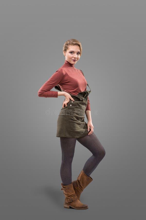 Взгляд моды девушки одел в ботинках юбки и broun непринужденного стиля вкратце изолированных на серой предпосылке стоковые изображения