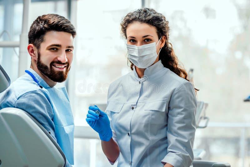 Взгляд молодого привлекательного дантиста explaning его работа к пациенту стоковые изображения