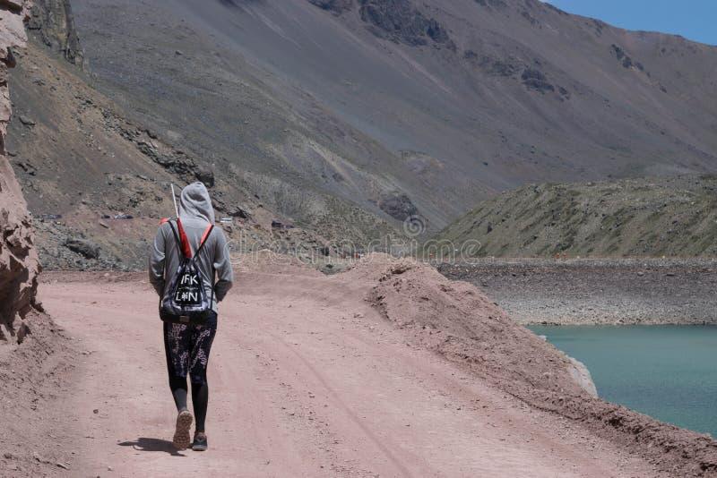 Взгляд молодой женщины идя вниз с грязной улицы в горной области стоковые изображения rf