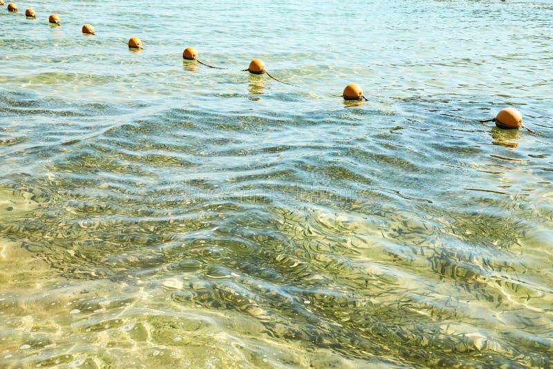 Взгляд моря от берега с длинной очередью оранжевой покрашенной отметки ставит бакены плавать стоковые фотографии rf