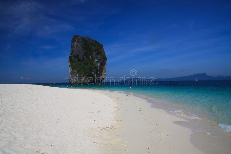 Взгляд над белым ярким пляжем песка на сиротливой известковой скале в темносинем море Andaman около Ao Nang, Krabi, Таиланда стоковое изображение