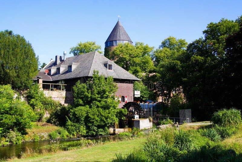 Взгляд над зеленым парком на водяной мельнице и башне средневекового замка, зеленых деревьев с голубым небом стоковое фото