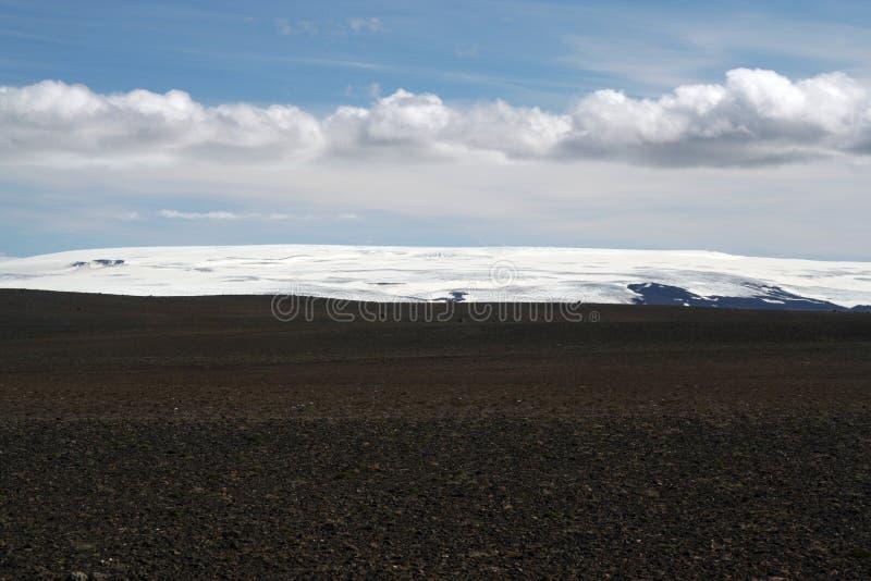 Взгляд над черной широкой бесконечной черной неурожайной пустошью со снегом покрыл горы - Исландию стоковые изображения