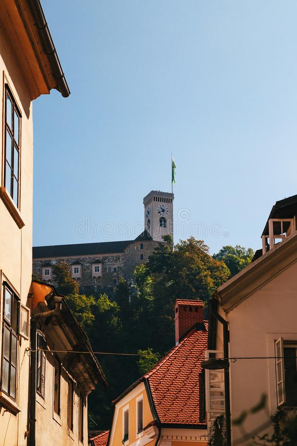 Взгляд на башне замка Любляны от красивой тихой узкой улочки с оранжевыми крыть черепицей черепицей крышами без людей в старой стоковые изображения rf