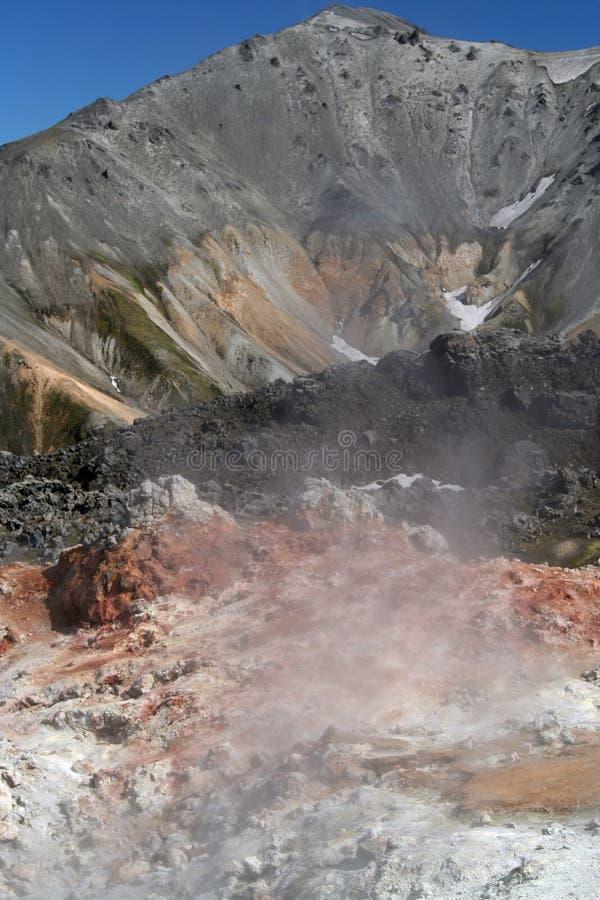 Взгляд на долине с красочными красными, белыми и черными дымя камнями с изрезанной серой стороной горы сравнивая с безоблачным го стоковое фото