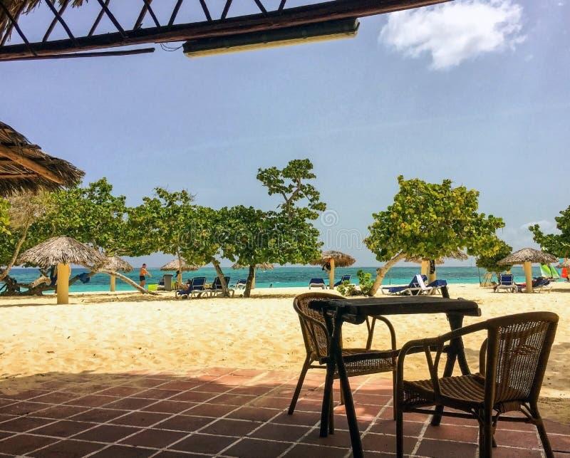 Взгляд на занятом тропическом пляже изнутри ресторана стоковое фото