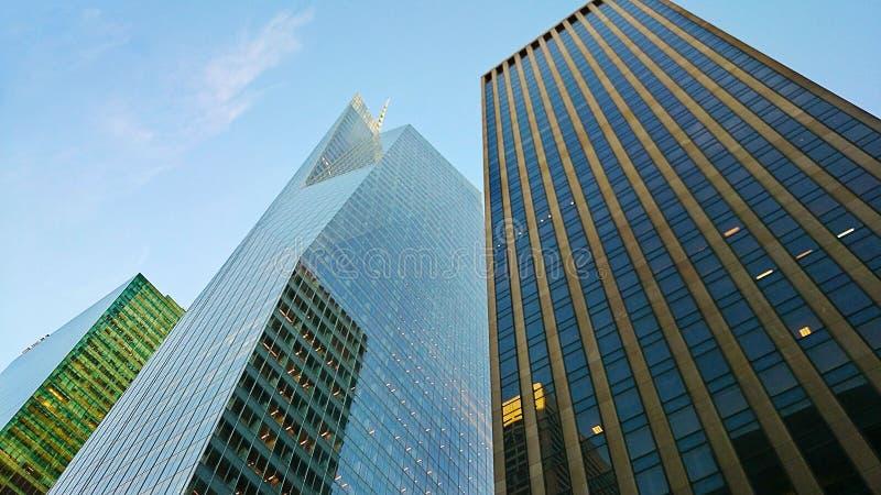 Взгляд на зданиях Манхаттана на голубом небе и белизне заволакивает предпосылка New York США стоковые изображения rf