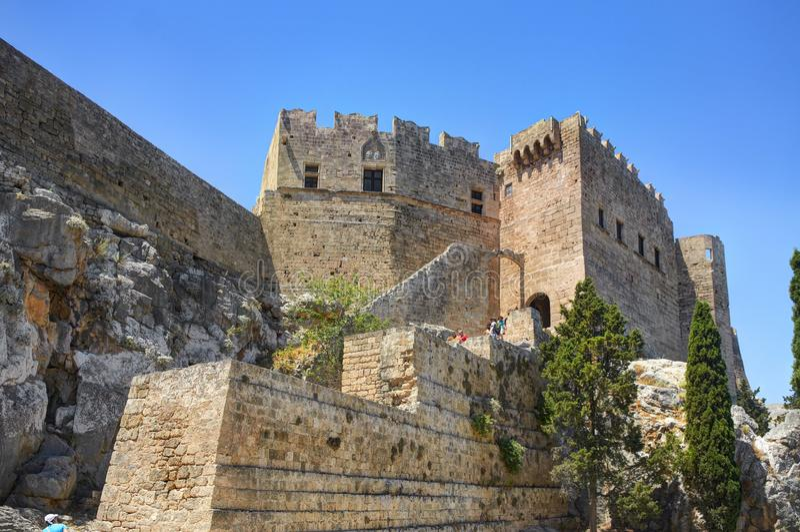 Взгляд на известных античных греческих руинах виска на утесе на острове Родосе Греции в городе Lindos и идя туристах Известное si стоковые изображения