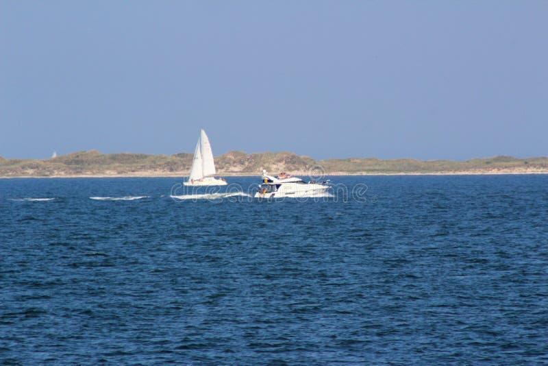 Взгляд на море и белой шлюпке под голубым небом на северном juist Германии острова моря стоковое фото rf