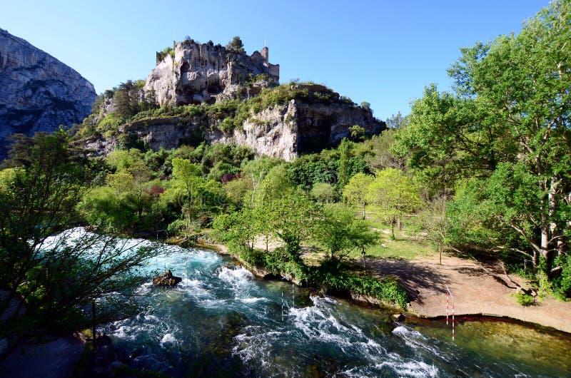 Взгляд на небольшом touristic провансальском городке с изумрудно-зелеными водами реки Sorgue и некоторых средневековых руин на стоковые фотографии rf