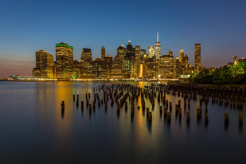 Взгляд на небоскребах в более низком Манхаттане от горизонта Бруклина в Нью-Йорке на ноче стоковые изображения rf