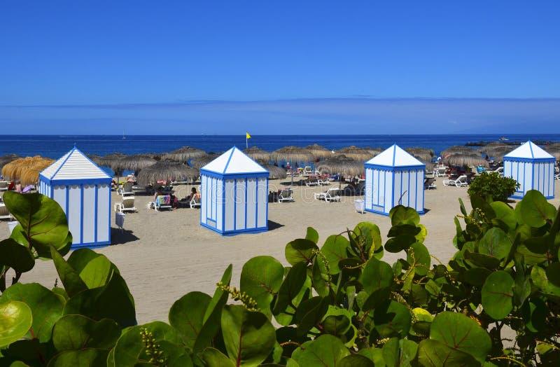 Взгляд на пляже El Duque с пляжными домиками в Косте Adeje, Тенерифе, Канарских островах, Испании стоковое фото rf
