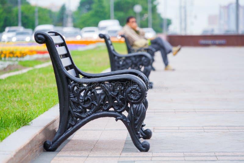 Взгляд на строке стендов в парке города с человеком сидя в нерезкости стоковая фотография rf